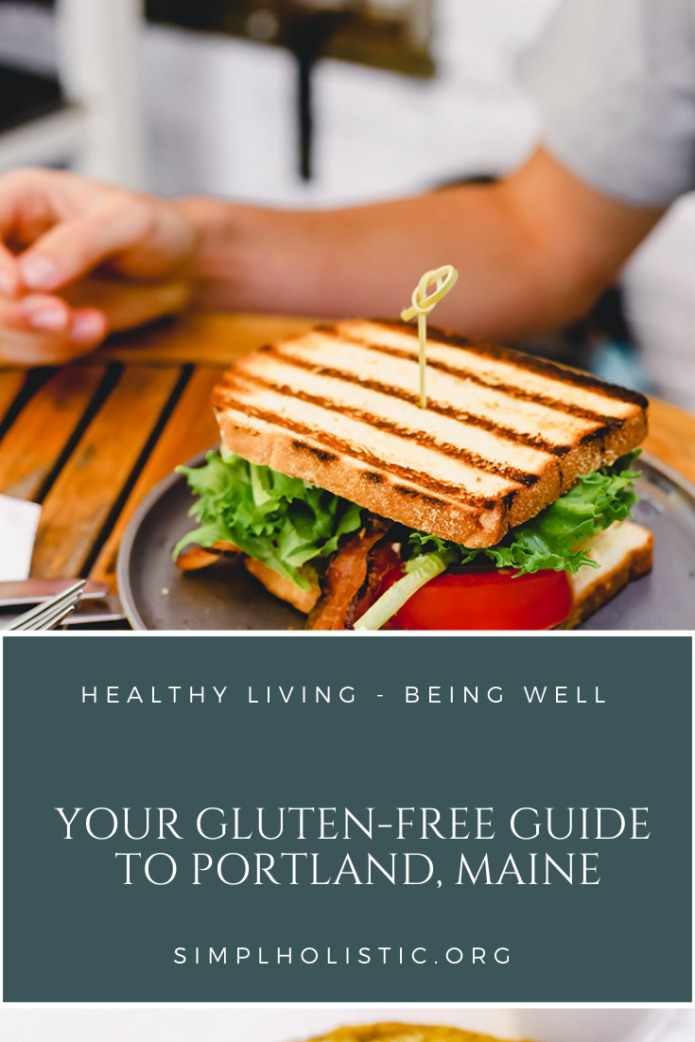 Your gluten free guide to Portland Maine in text over a dark blue box with white words. The background is a picture of a grilled sandwich with tomato and greens portland maine gluten free